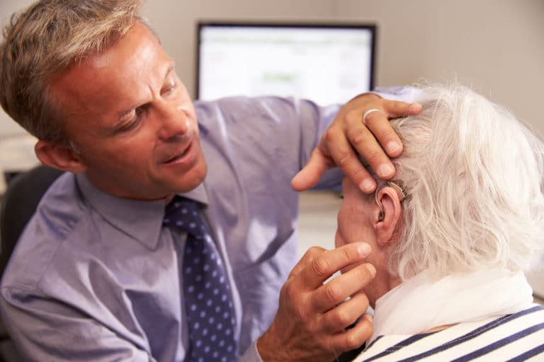 Man being fit with a hearing aid