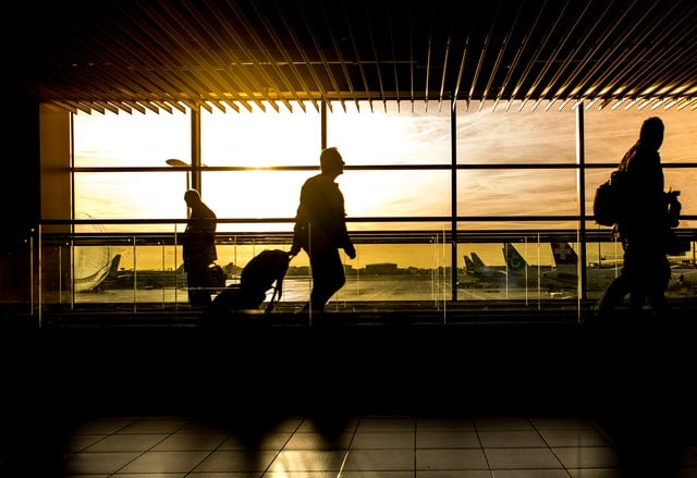 Man wheeling a suitcase through an airport
