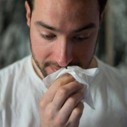 man holding a tissue to his nose