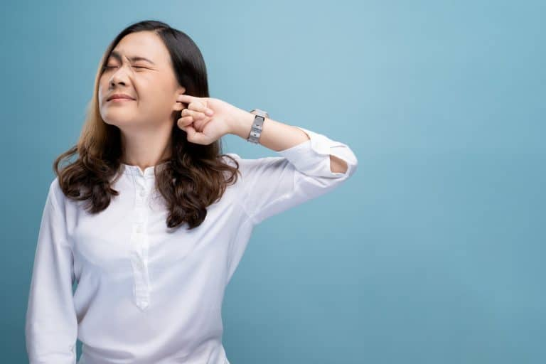 Woman putting a finger into her ear