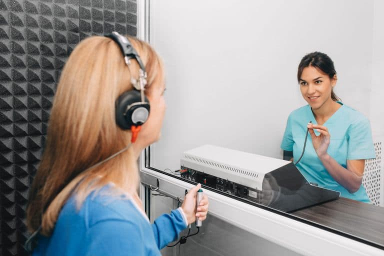 woman participating in a hearing test in a sound proof room looking through a glass panel at a female audiologist