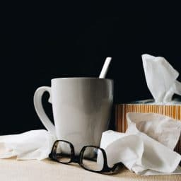 A mug, a pair of glasses and box of tissues.