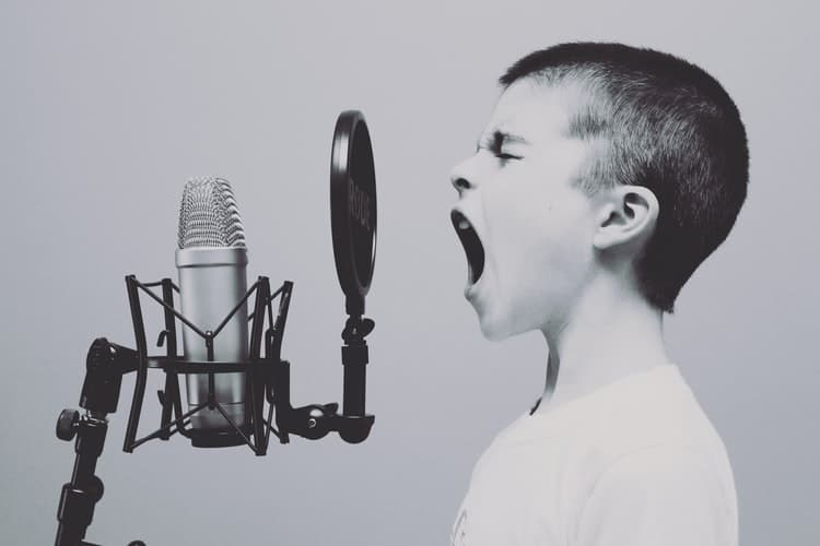 Boy singing into microphone.