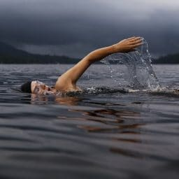 Man swimming in a lake.